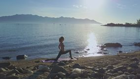 Flycam Side View Girl Does Yoga against Rising Sun Sea. Flycam side view girl silhouette does yoga on beach against pictorial rising sun and tranquil sea stock video footage