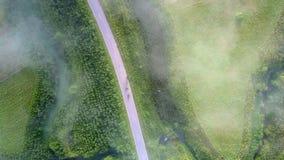 Flycam stiger ned till vägen med trafik bland grönt landskap arkivfilmer