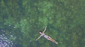 Flycam toont Meisje het Zwemmen in Transparante Overzees onder Zonlicht stock footage