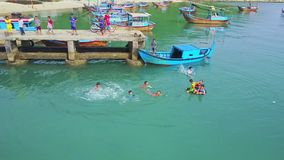 Flycam view Asian children play jump and swim in azure water stock footage