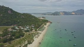 Flycam view coast boats sail in ocean against distant peninsula stock video