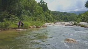 Flycam View Fisher Swims in River Takes out Net against Tropics stock footage