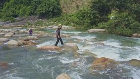 Flycam View Fishermen with Caught Fish in Bags Jump on Stones stock footage