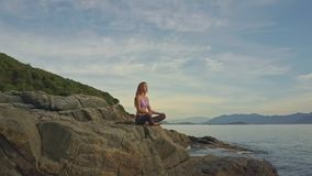 Flycam view girl sits in yoga pose against hills on ocean coast stock video