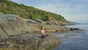 Flycam view girl sits in yoga pose against sea tide to rocks. Flycam removes from girl sitting in yoga pose Ardhapadmasana on beach against sea tide to rocks and stock video