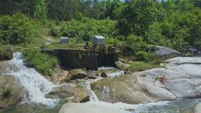 Flycam View Hydroelectric Power Station Made by Local People. Against powerful rapids under sun rays stock video