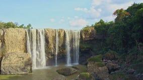Flycam visar vattenfallet från överkant mot himmel längs stenväggen stock video