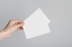 A6 Flyer / Postcard / Invitation Mock-Up. Male hands holding blank flyers on a gray background Stock Photos