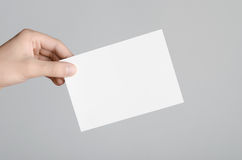A6 Flyer / Postcard / Invitation Mock-Up. Male hands holding blank flyers on a gray background Stock Photography