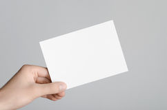 A6 Flyer / Postcard / Invitation Mock-Up. Male hands holding blank flyers on a gray background Stock Photo