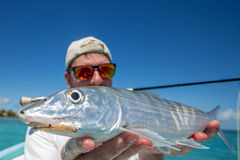 Flyfisher holding a Bonefish. A man holding a Boneifhs fish caught a fly, somewhere on the flats of Belize next too a mangrove Stock Photos