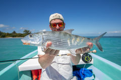 Flyfisher holding a Bonefish. A man holding a Bonefish caught a fly, somewhere on the flats of Belize next too a wonderful coas Stock Photography