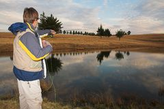 Flyfishing #14. A fly fisherman casting a line in Dullstroom, South Africa Stock Image