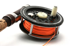 Flyfishing Reel. A well used flyreel and rod beckons to head outdoors and hit the water Royalty Free Stock Photography