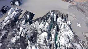Flyg över den Solheimajokull glaciären i sydliga Island Flyg- surrsikt av sprickan och den svarta vulkaniska askaen som fångas i  stock video