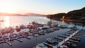 Flyg över fartyg i en marina på solnedgången arkivfilmer