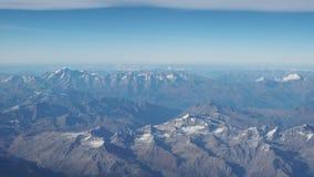 Flyg över fjällängarna under nedgångsäsong Landskap på Mont Blanc och glaciärerna Flyg- sikt från flygplanfönstren lager videofilmer