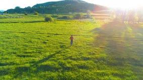 Flyg över sportman på den perfekta ängen för grönt gräs Solnedgång i berg lager videofilmer