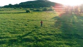 Flyg över sportman på den perfekta ängen för grönt gräs Solnedgång i berg arkivfilmer