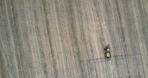 Flyg över traktorsprejaren med långa stänger som är rörande på fält arkivfilmer