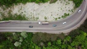Flyg- överkant ner sikt av en skog för granträd och en lantlig bilväg arkivfilmer