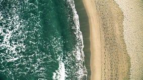 Flyg- överkant ner sikt av havsbränning på stranden med många fotspår stock video