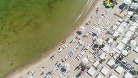 Flyg- överkant ner sikt på en stadsstrand Folkmassa av folk som vilar och simmar på den härliga stranden nära havet, lager videofilmer