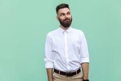 Flyg av tankar Fundersam skäggig affärsman som ser bort, medan stå mot ljus - grön vägg Fotografering för Bildbyråer