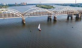 Flyg- bästa sikt av den Darnitsky bron, yachter och fartyg som seglar i den Dnieper floden från över, Kiev Kyiv stadshorisont Royaltyfri Bild