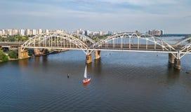 Flyg- bästa sikt av den Darnitsky bron, yachter och fartyg som seglar i den Dnieper floden från över, Kiev Kyiv stadshorisont Fotografering för Bildbyråer