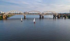 Flyg- bästa sikt av den Darnitsky bron, yachter och fartyg som seglar i den Dnieper floden från över, Kiev Kyiv stadshorisont Arkivfoto