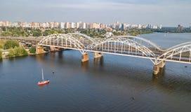 Flyg- bästa sikt av den Darnitsky bron, yachter och fartyg som seglar i den Dnieper floden från över, Kiev Kyiv stadshorisont Arkivbilder