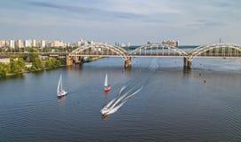Flyg- bästa sikt av den Darnitsky bron, yachter och fartyg som seglar i den Dnieper floden från över, Kiev Kyiv stadshorisont Royaltyfria Foton