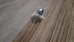 Flyg- bästa sikt av en traktor, skördetröska som på våren plogar jordbruks- land royaltyfri bild