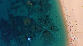 Flyg- bästa sikt av folk som solbadar och simmar på den berömda vita stranden lager videofilmer