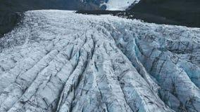 Flyg- bästa sikt av kanterna av den vita glaciären med den svarta askaen lager videofilmer