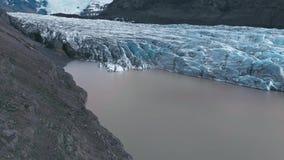 Flyg- bästa sikt av kanterna av den vita glaciären med den svarta askaen och en sjö stock video