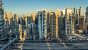 Flyg- bästa sikt för Dubai marinaskyskrapor under soluppgång från JLT i den Dubai natten till dagtimelapse, UAE arkivfilmer
