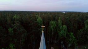 Flyg- cirkel för bästa sikt runt om kors av den härliga kyrkan i Jurmala under guld- timmesolnedgång - Sala Sv Janis ev stock video