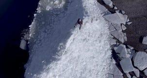 Flyg- dronsikt av den unga aktiva lyckliga mannen som blir på isglaciärerna nära kustlinjen av vinterhavet surrsikt arkivfilmer