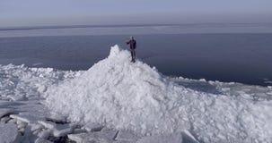 Flyg- dronsikt av den unga aktiva lyckliga mannen som blir på isglaciärerna nära kustlinjen av vinterhavet som väver handen arkivfilmer