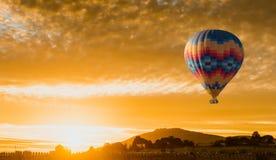 Flyg för ballong för varm luft på gul soluppgång royaltyfria bilder