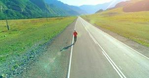 Flyg för låg höjd framme av den sportiga mannen på den perfekta asfaltvägen lager videofilmer