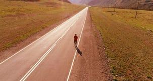 Flyg för låg höjd framme av den sportiga mannen på den perfekta asfaltvägen arkivfilmer