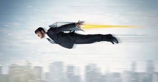 Flyg för Superheroaffärsman med strålpackeraket ovanför citen Fotografering för Bildbyråer