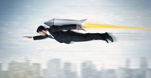 Flyg för Superheroaffärsman med strålpackeraket ovanför citen Arkivfoton