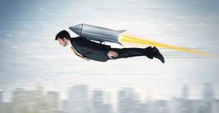 Flyg för Superheroaffärsman med strålpackeraket ovanför citen Royaltyfria Bilder