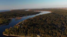 Flyg- flod Lielupe in i golf för baltiskt hav i Varnukrogs - bästa sikt för guld- timmesolnedgång från ovannämnt - surr som skjut lager videofilmer