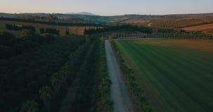 Flyg- flyg över den lantliga vägen och kullar på solnedgången Royaltyfria Bilder