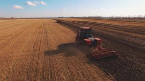 Flyg- fors 4k av inflyttningen för två traktorer ett plogat fält och skörda arkivfilmer